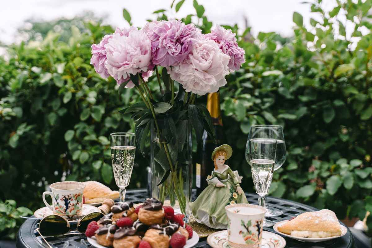 breakfast table with profiteroles and champagne glasses decorated with flowers bouquet and figurine in garden
