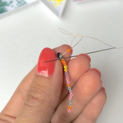Le tissage brick stitch : Enfilez la 3ème perle de la rangée, la orange. Passez votre aiguille sous le fil juste à côté.