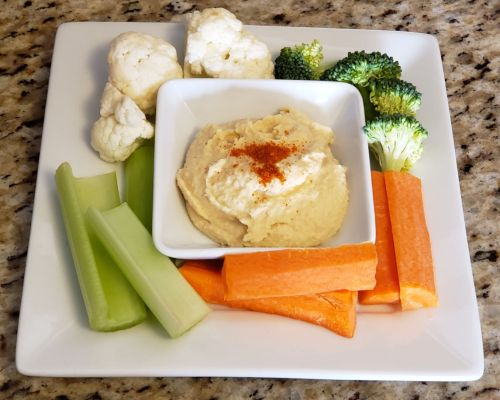 Plate of hummus, topped with paprika and surrounded by vegetables