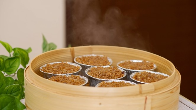 A bamboo steamer that has 7 Lo Mai Gai in it