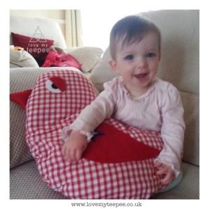little girl holding a big red bird cushion