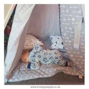 baby asleep on the floor mat inside his grey bespoke teepee