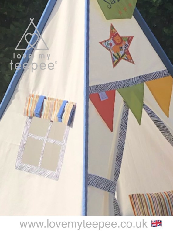 ivory teepee with blue pole cases bright door flags and a stipped window blind