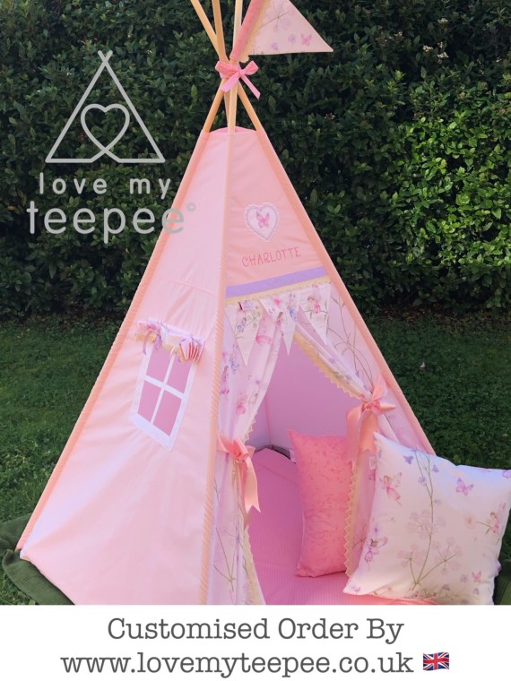 pink fairyland teepee trimmed in lilac. Heart + name above the door flags, two cushions pink fairy frost and white fairy. Window with a blind + large pole flag