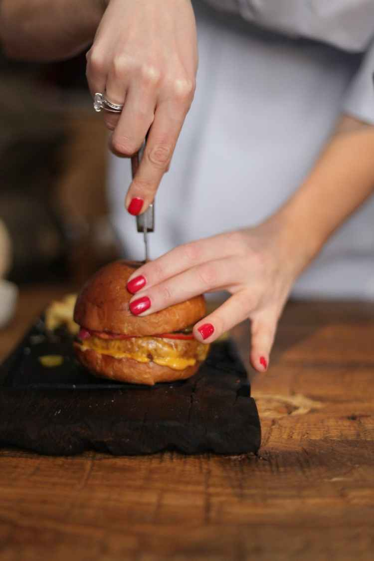 person holding a knife slicing a burger