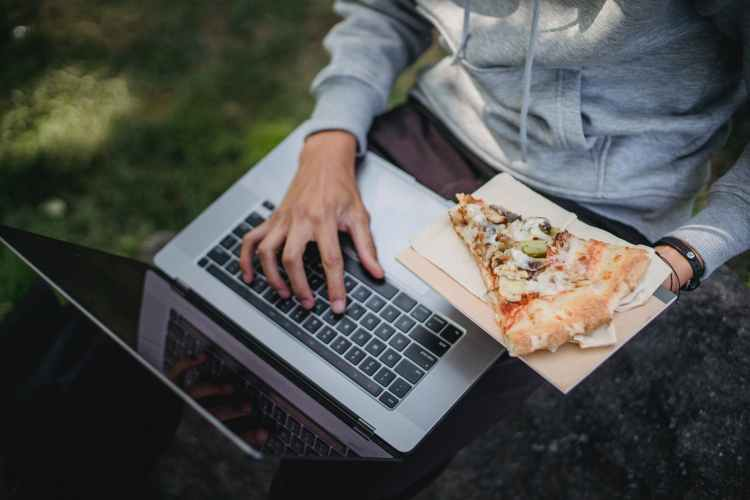 male student typing text on laptop and eating pizza