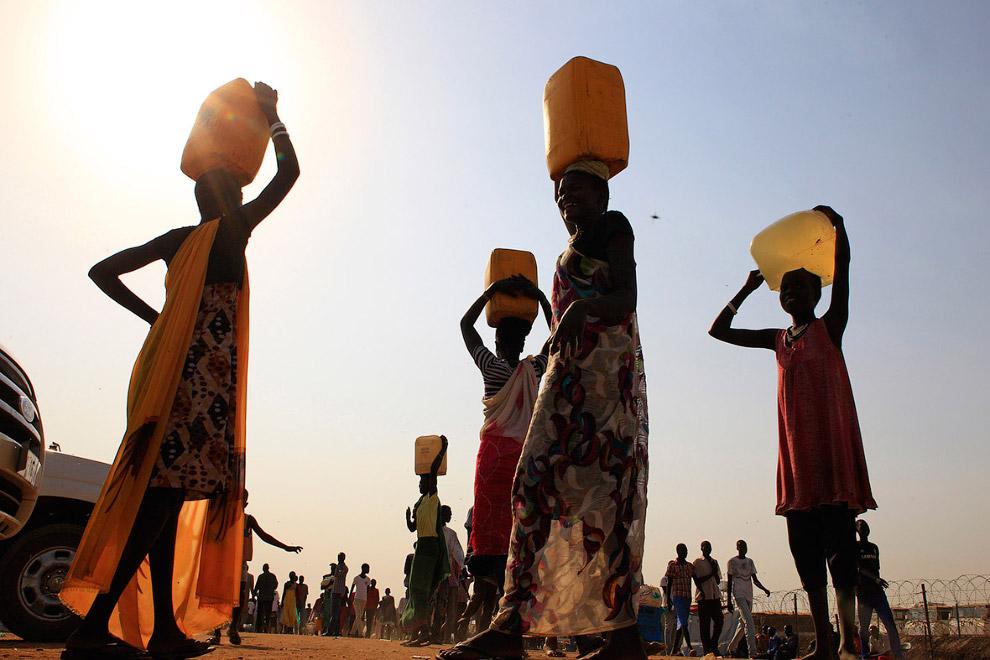 Переноска воды недалеко от столицы Южного Судана. И от солнца спасает