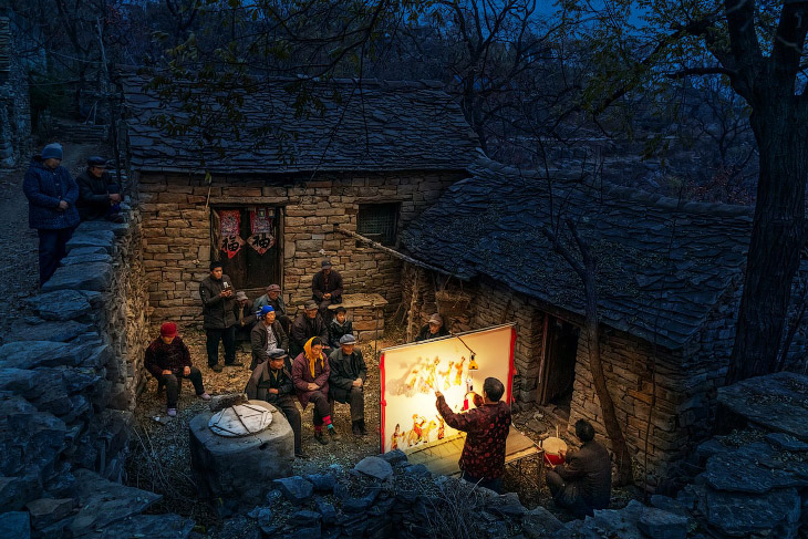 Представление для местных жителей во дворе каменного дома в Китае