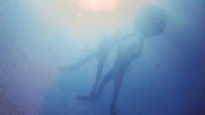 浮き輪に捕まり青の洞窟を進むカップル