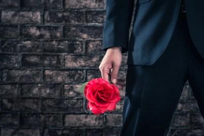 バラの花を持っているスーツのチャラ男
