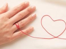 女性の手と赤い糸