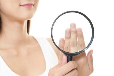 拡大鏡でネイルを見る女性