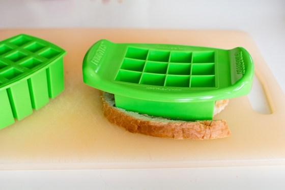 Je zet het bakje met vierkantjes over je boterham en dan druk je het een keer of wat goed aan.