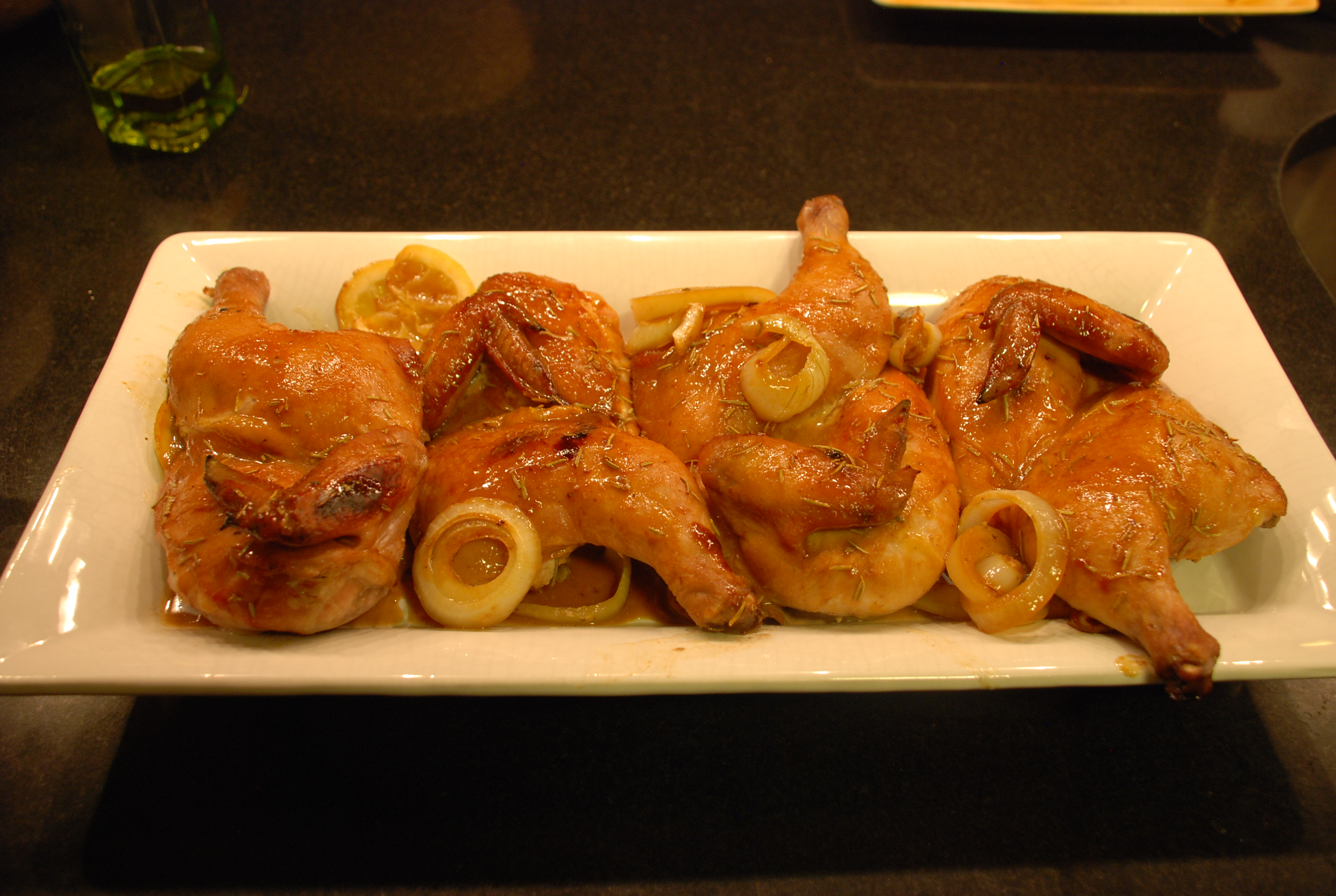 Mustard teriyaki cornish hens on a white plate.