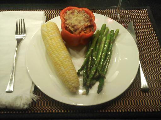 Stuffed peppers, corn, and asparagus on a white plate.