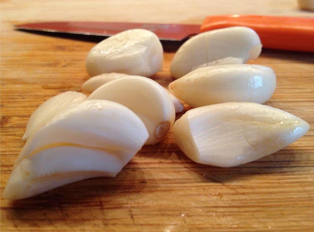 Garlic cloves on a wooden cutting board.