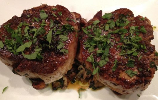 Garam masala pork chops with mushrooms and fresh herbs on a white plate.