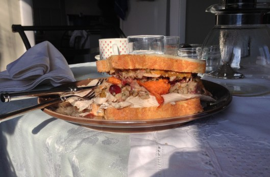 Thanksgiving leftovers in a gobbler sandwich with turkey, sweet potatoes, stuffing, gravy, mayonnaise and cranberry sauce on it.