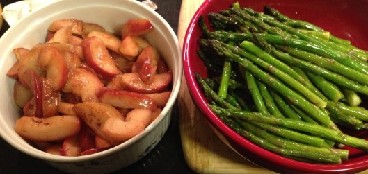 Sauteed apples in butter with cinnamon, nutmeg and lemon; roasted asparagus with olive oil and lemon in a red holiday bowl.