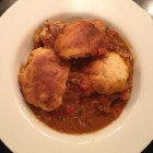 Chicken goulash with biscuit topping in a white bowl.