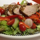Red leaf lettuce salad with tomatoes, red peppers, tomatias, cucumber and roasted pork tenderloin.