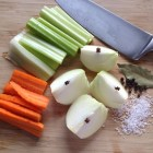 Ingredients for homemade chicken stock on a wooden cutting board.
