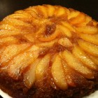 Beautiful pear upside down cake on a white Wedgewood plate.