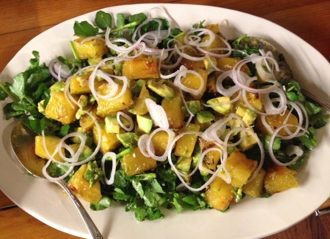 Grilled pineapple, avocado, and watercress salad with sliced shallots and a cumin vinaigrette dressing on a white platter.