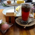 Rooibos tea in a theral glass with rock candy on a stick, with a tea timer and macaroons.