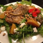 Dinner salad with roast chicken leg, roasted yellow beets, feta cheese and toasted pine nuts on a white Wedgewood plate.