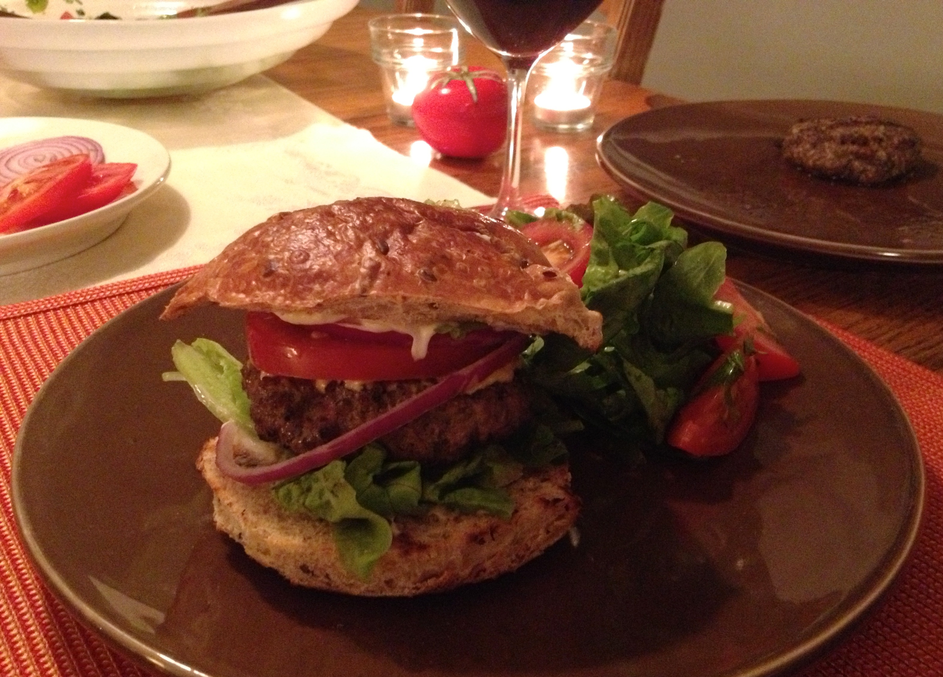 Grilled lamb burger on a bun with lettuce, tomato and red onion on a brown plate.