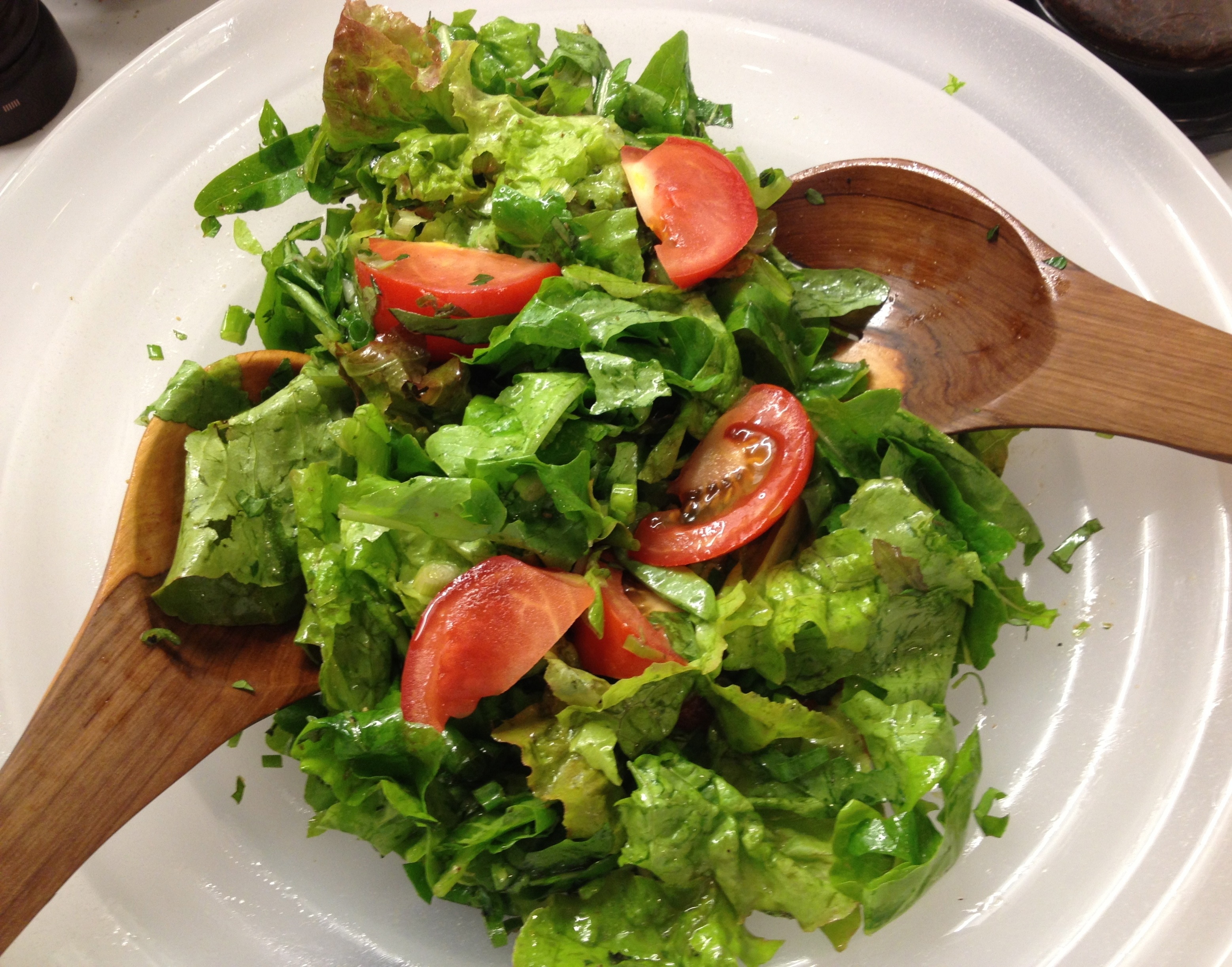 Mixed leaf lettuces with tomatoes in a serving bowl with African wooden serving spoons.