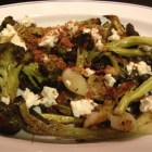 Broccoli and spring onions, oven roasted and topped with feta and toasted bread crumbs on a white French platter with blue trim.