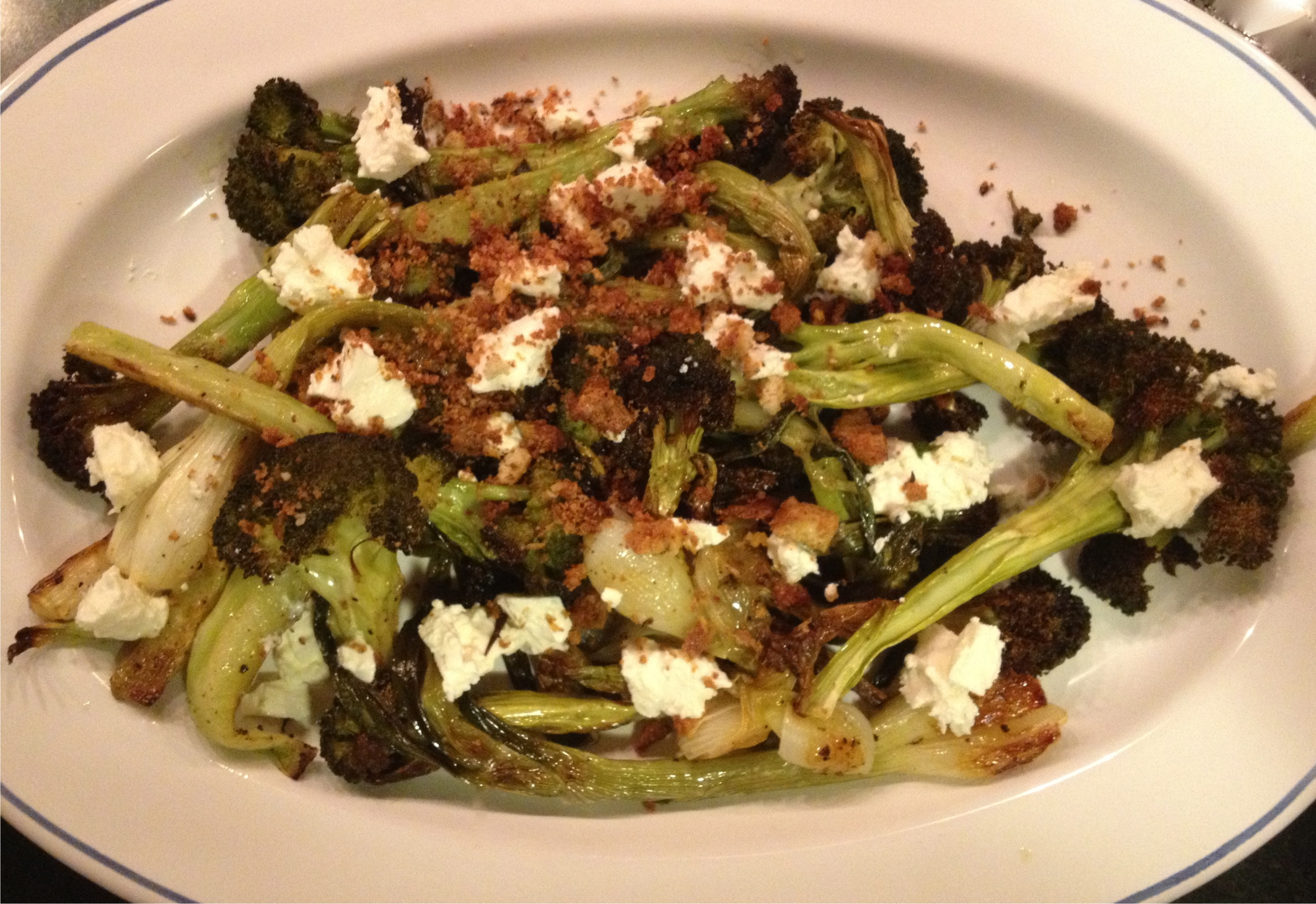 Roasted broccoli and spring onions with feta and toasted bread crumbs on a white French platter.