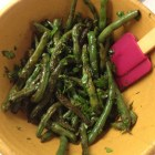 Green beans with fresh basil in a yellow ware bowl with a maroon spatula.