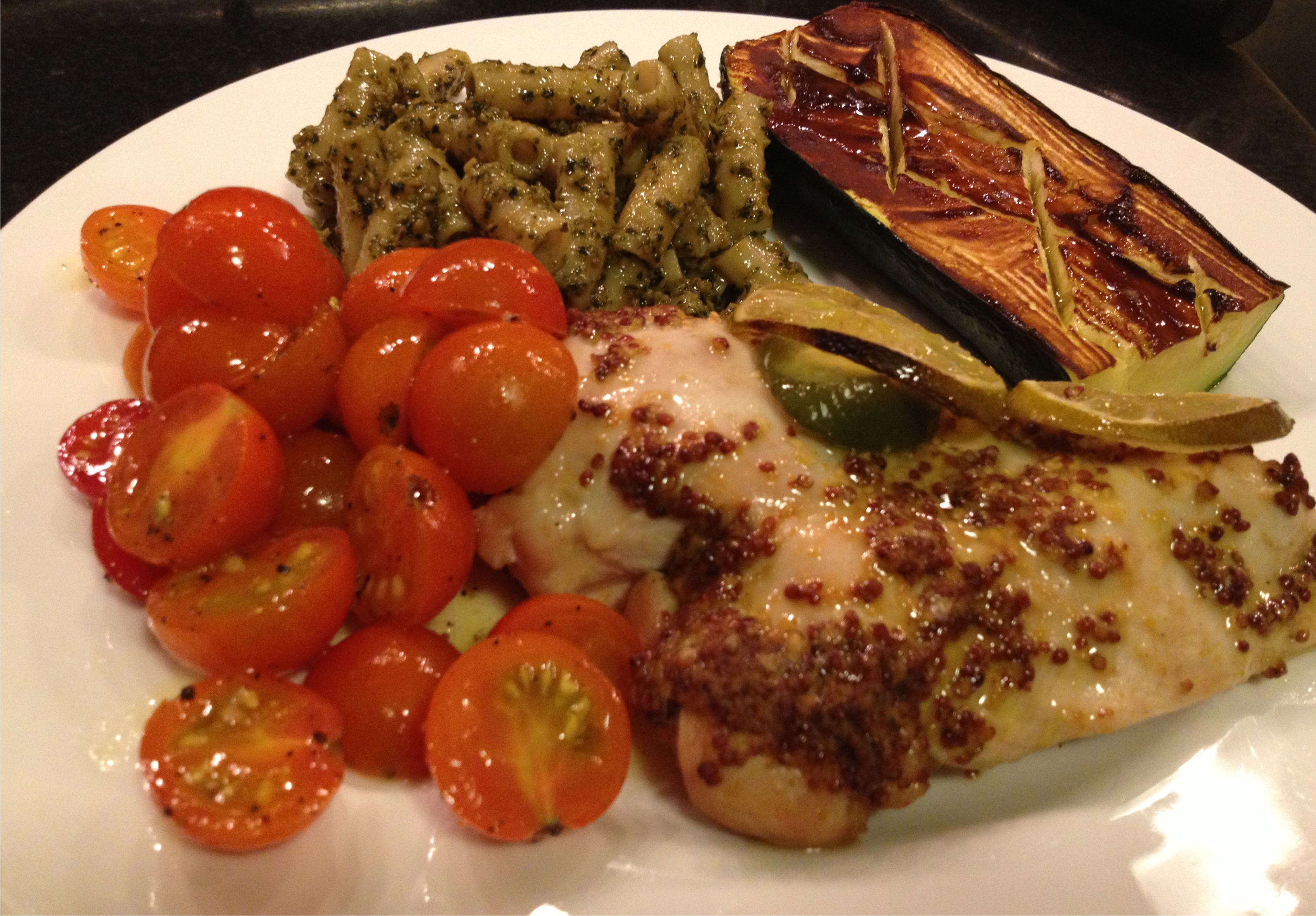 Tamarind glazed squash, grainy mustard coated chicken breast with brown rice pasta with pesto and sunny gold farmer's market tomatoes on a white Wedgewood plate.