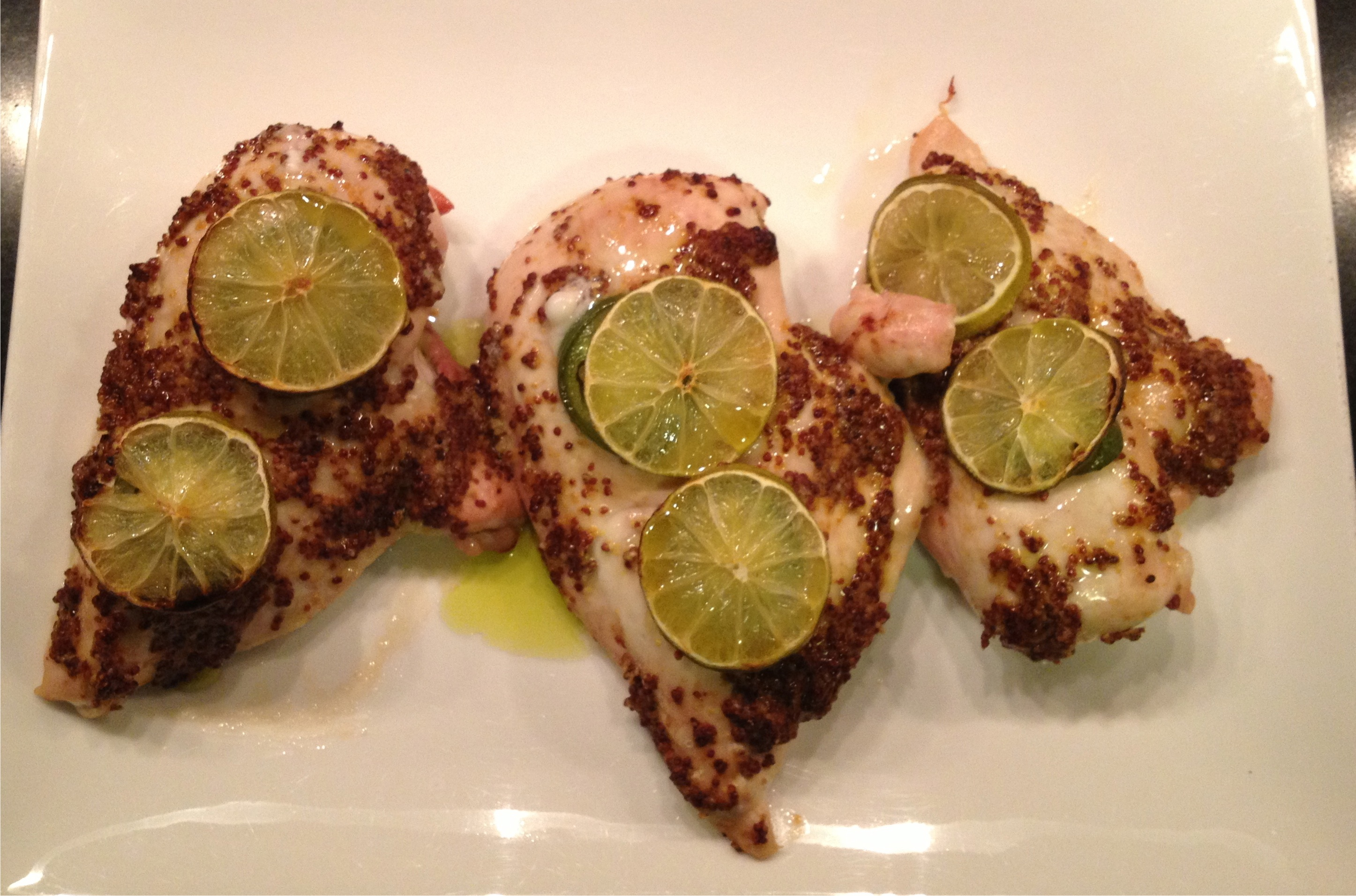 Grainy mustard coated chicken breast with jalapeno and limes on a white platter.
