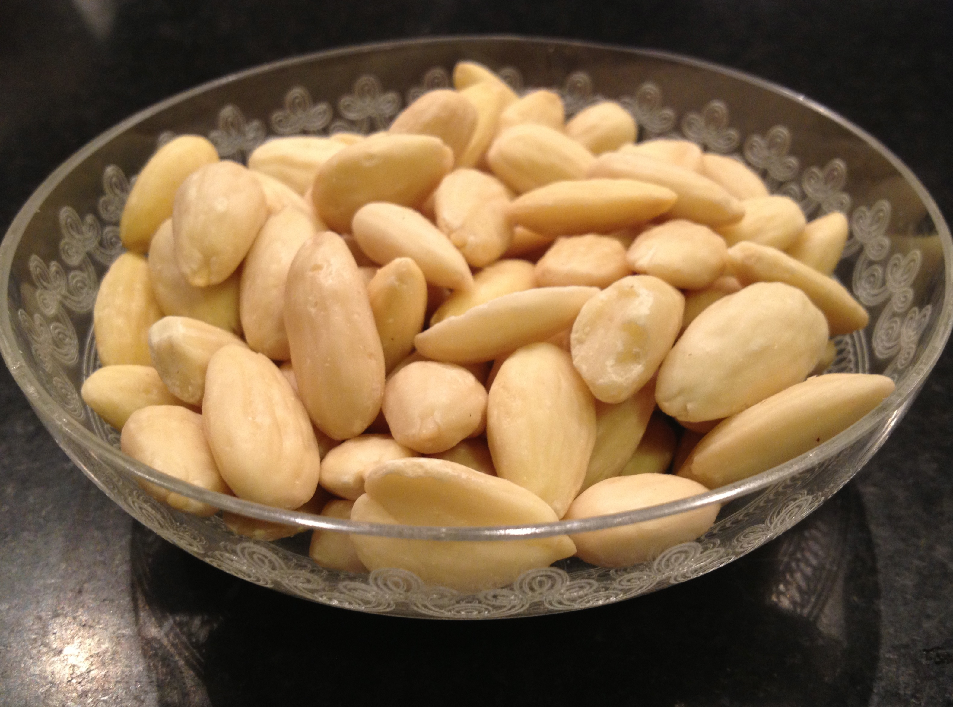 Raw almonds in a small crystal bowl.