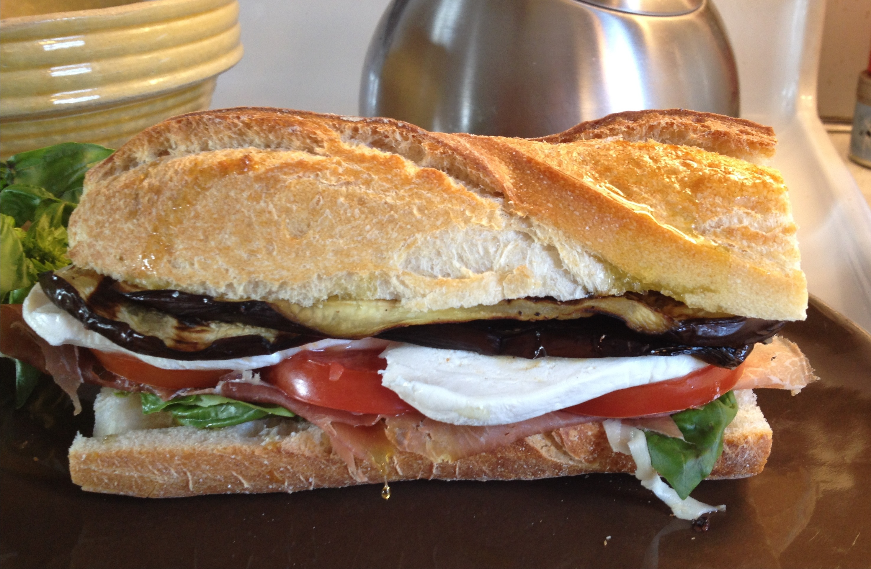 Grilled eggplant sandwich with mozzarella tomato basil and proscuitto