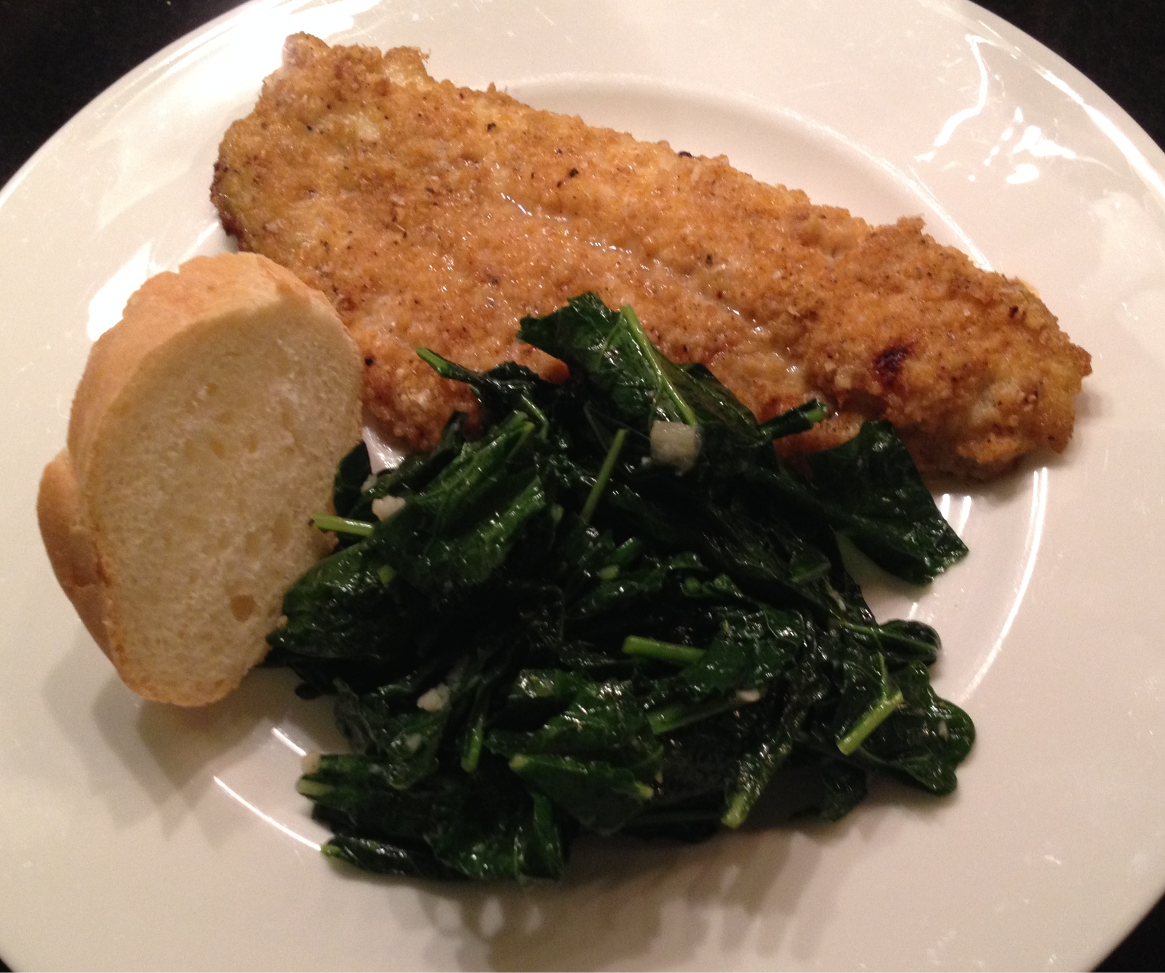Simply7 quinoa chip crusted catfish on a plate with sauteed kale and baguette piece.