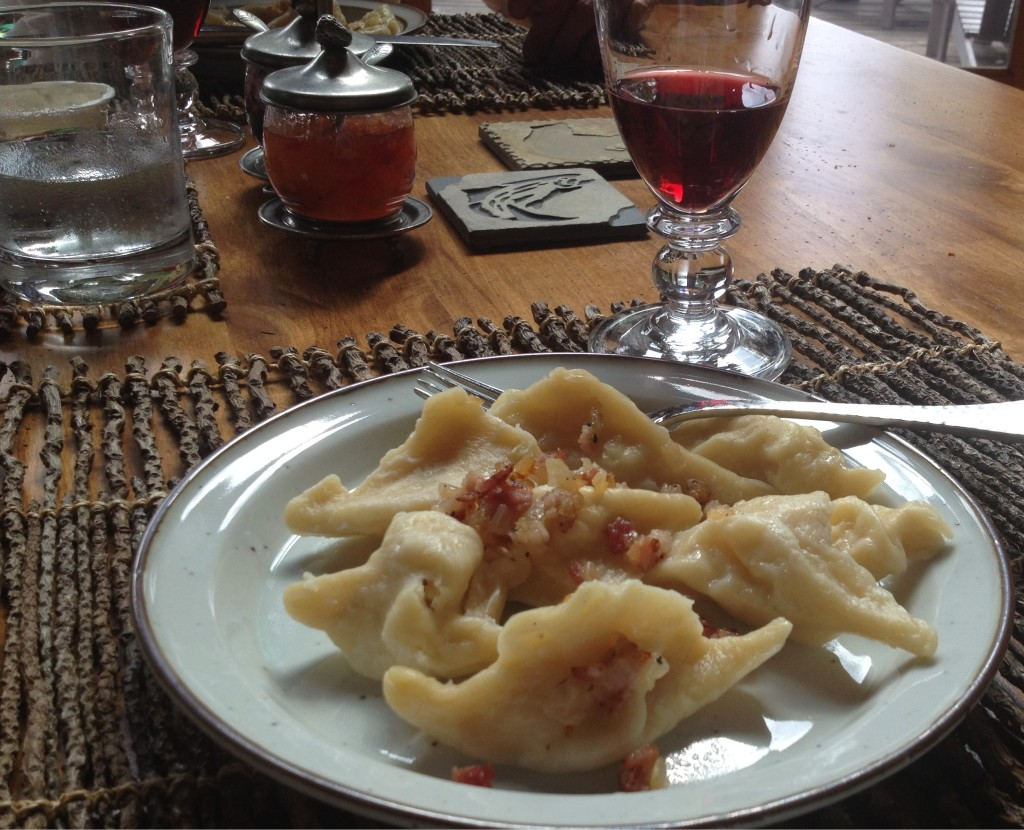 Pierogi on a plate with bacon and onion topping.