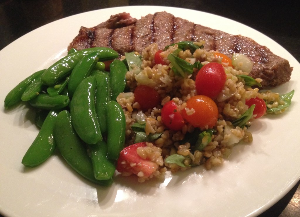 Freekeh salad on a plate with steak and sugar snap peas.