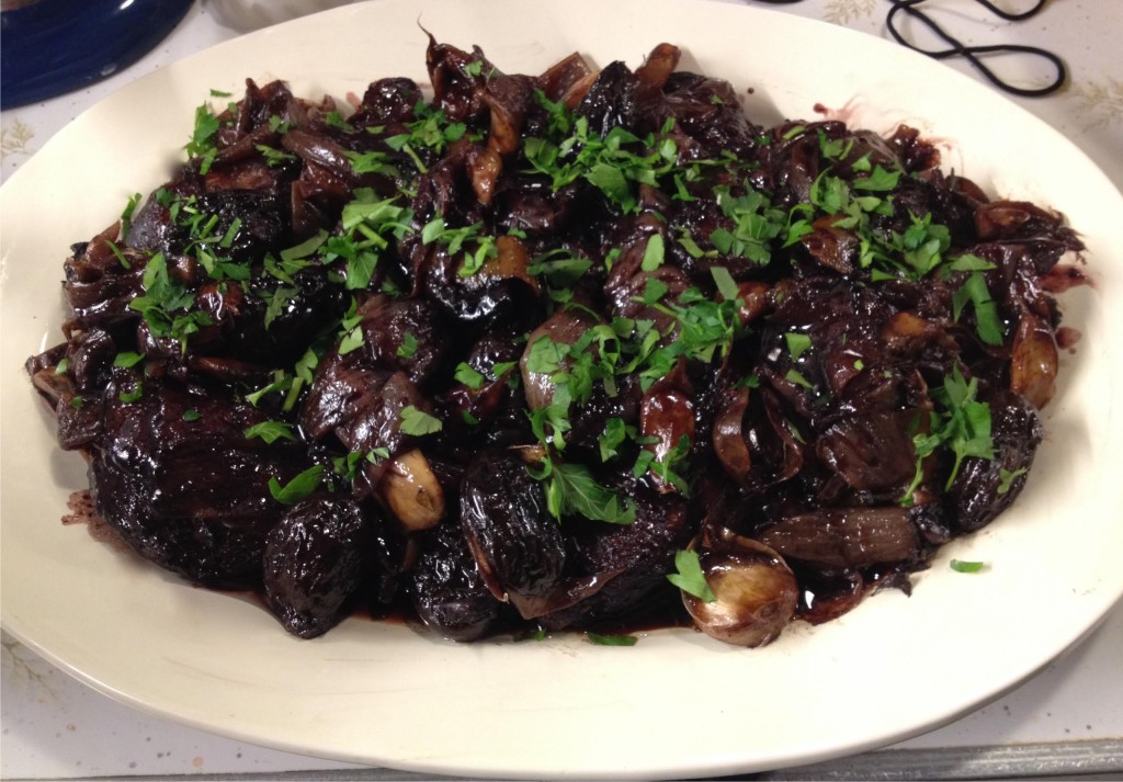 Duck braised with red wine and prunes on a white platter.