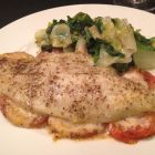 Catfish with tomatoes and horseradish on a plate with sauteed escarole.