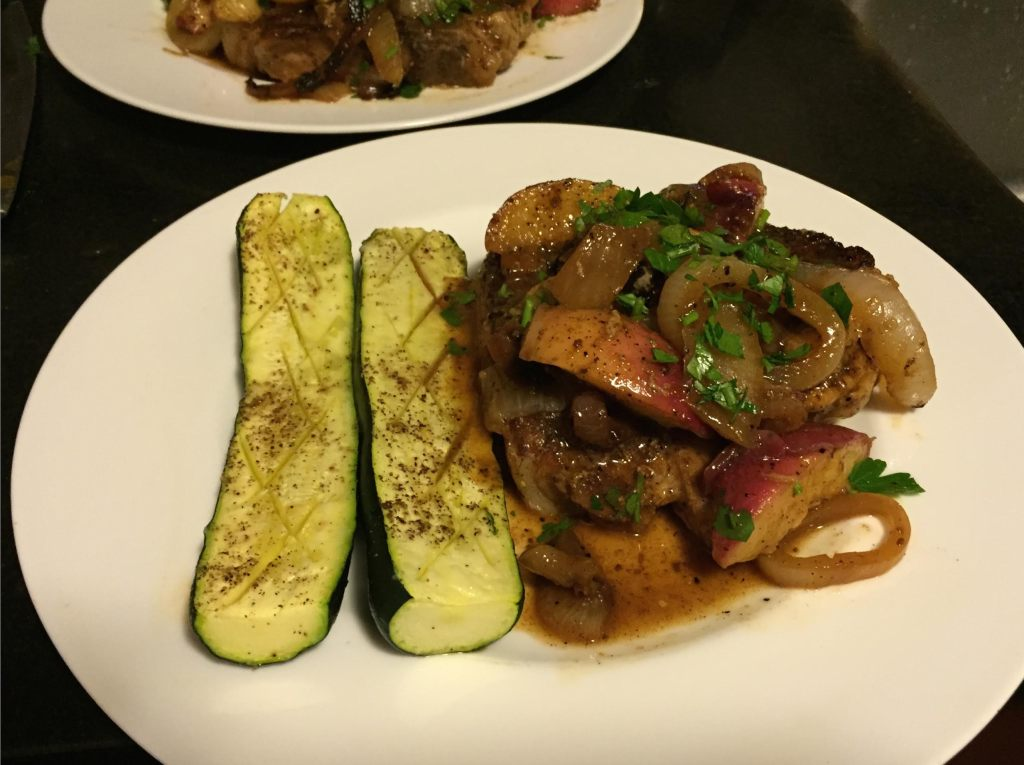 Pork and peaches on a plate with zucchini.