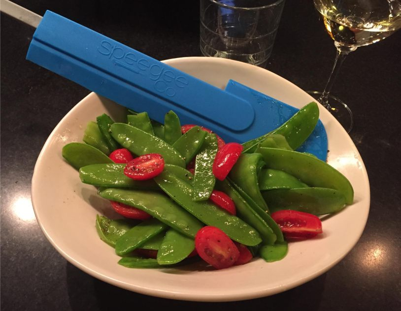 Speegee spatula in blue with snow peas and tomatoes in a Simon Pearce bowl.