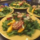 Arugula salad with grilled radishes, mango and mint with a Champagne vinaigrette on a yellow bordered plate.