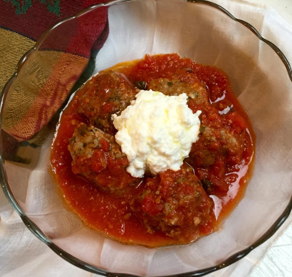 Meatballs made with veal & lamb in a rich tomato sauce topped with ricotta cheese in a glass bowl.