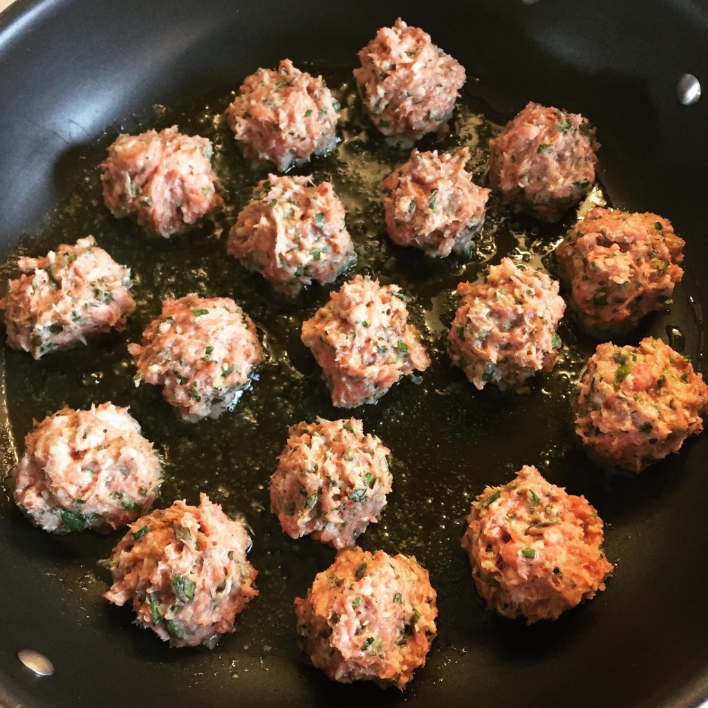 Lamb and veal meatballs with lots of herbs, frying in a skillet.