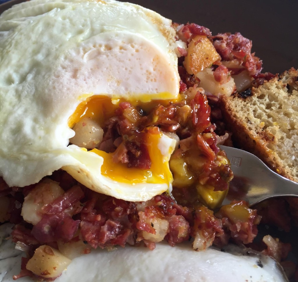 Corned beef hash with and over easy egg breaking the yolk over it.